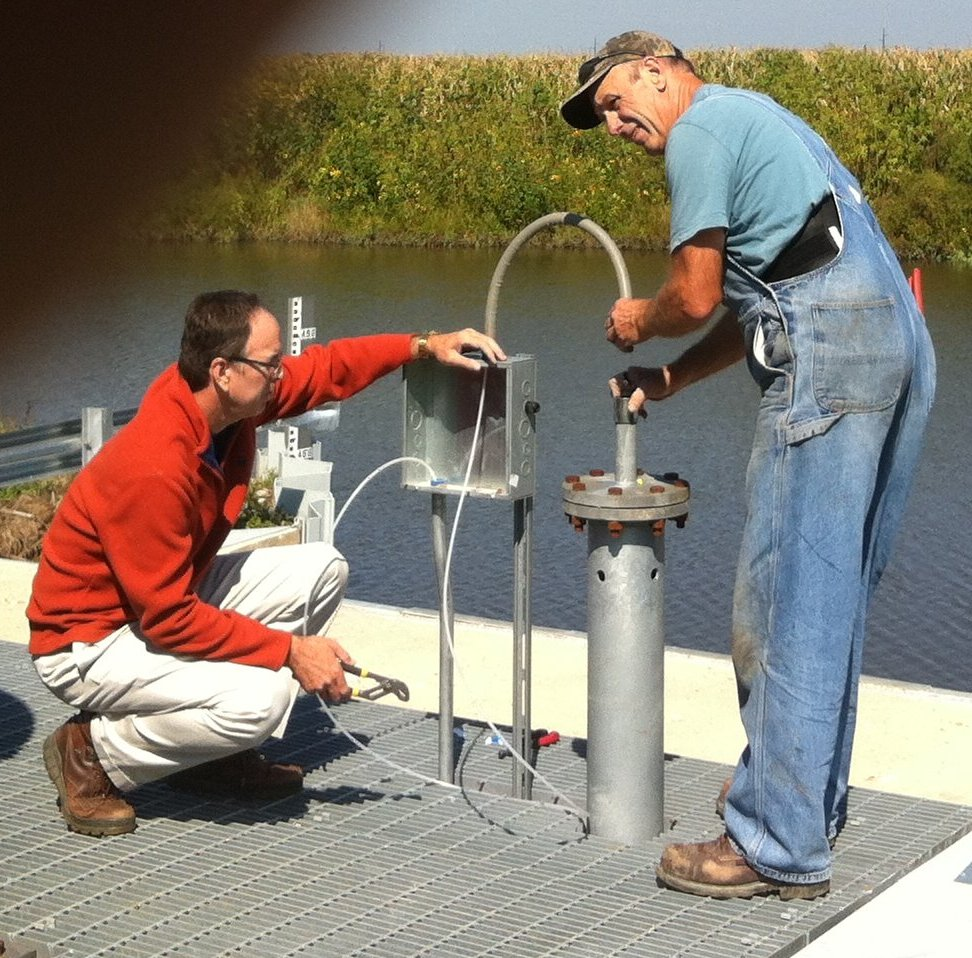 Installation of the Nylon Tubing into the Ditch-Side Stilling Well. Jim Mimlitz, Navionics Research (left), Hank Borrenpohl, Okawville Electric (right).